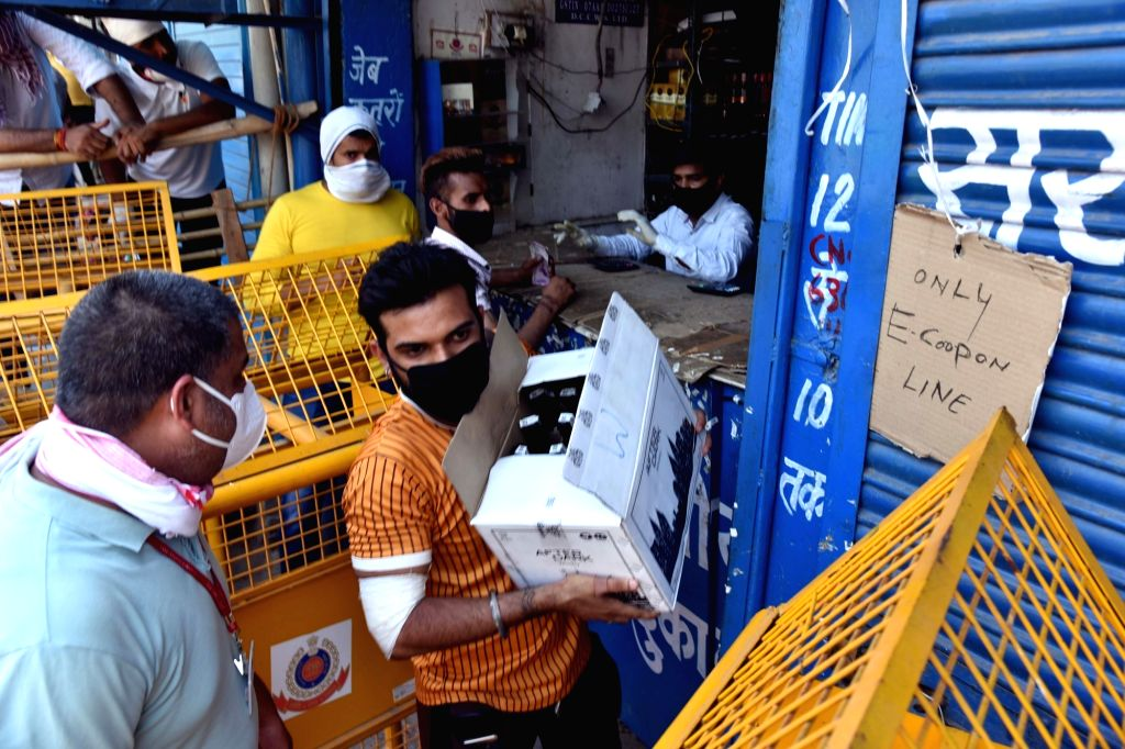 People gather in long queues to purchase liquor after Delhi govt had launched e-token system for the sale of liquor to avoid the overcrowding and practice the social distancing at a wine ...
