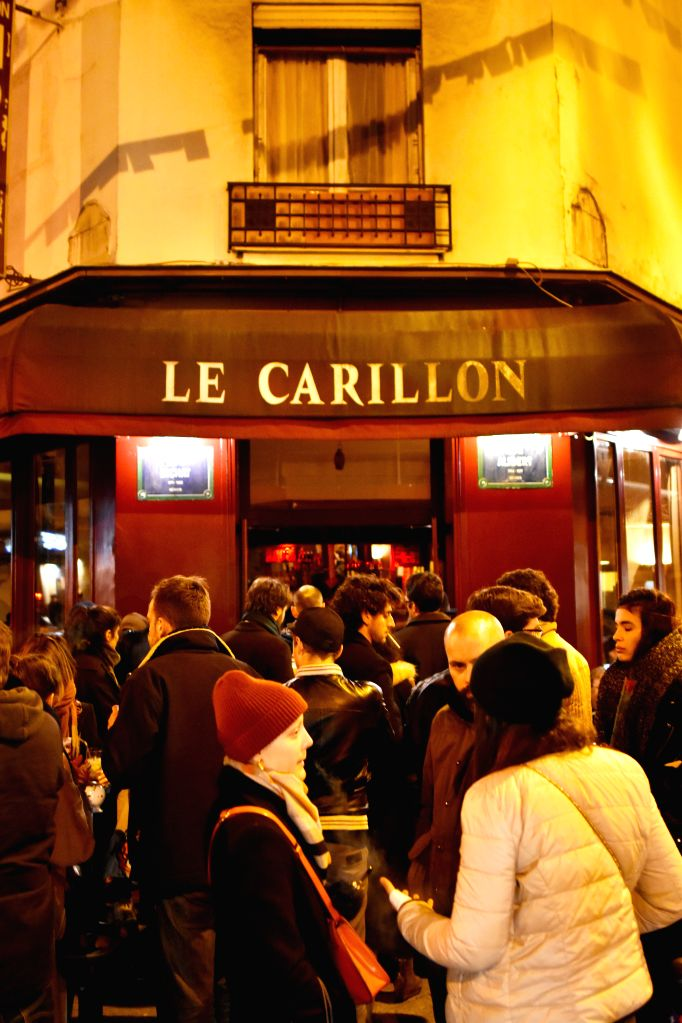 People gather outside Le Carillon restaurant, one of sites of the November 13 terror attacks in Paris, on Jan. 13, 2016, on its reopening day.  On Nov. 13, 2015, ...