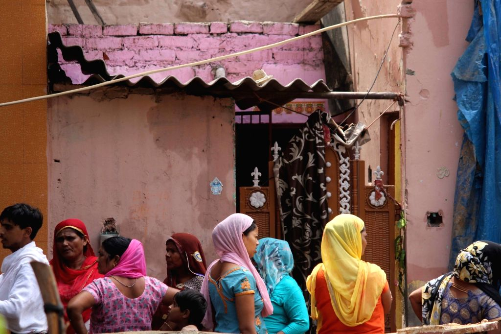 People gather outside the house, the roof of which collapsed at Dwarka's Hari Vihar area in New Delhi on July 23, 2018. Two members of a family were killed and three others were injured in ...