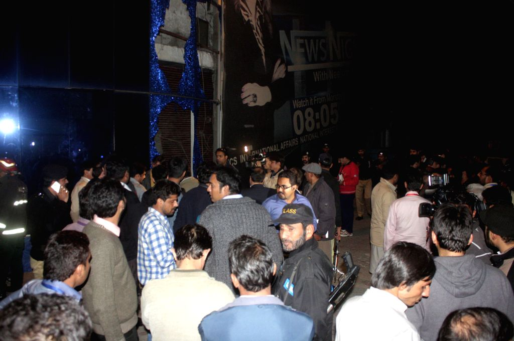 People gather outside the office of a local TV news channel after a grenade attack on Dec. 1, 2015. At least four people including two policemen were injured in a ...