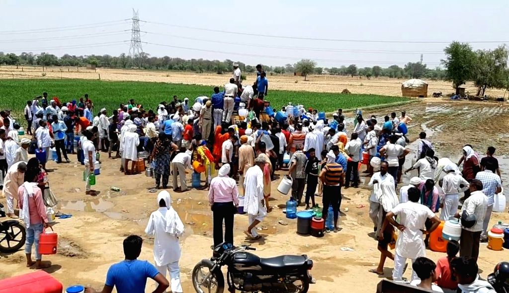 People gather to collect 'miracle' water that they believe is a panacea for several diseases, including diabetes, at Gujriwas village in Haryana's Rewari district, on June 7, 2019. Hundreds ...