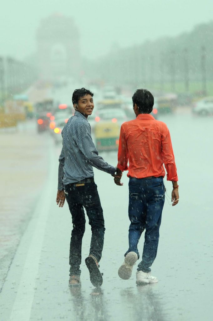 People get drenched during rains in New Delhi on July 2, 2014.