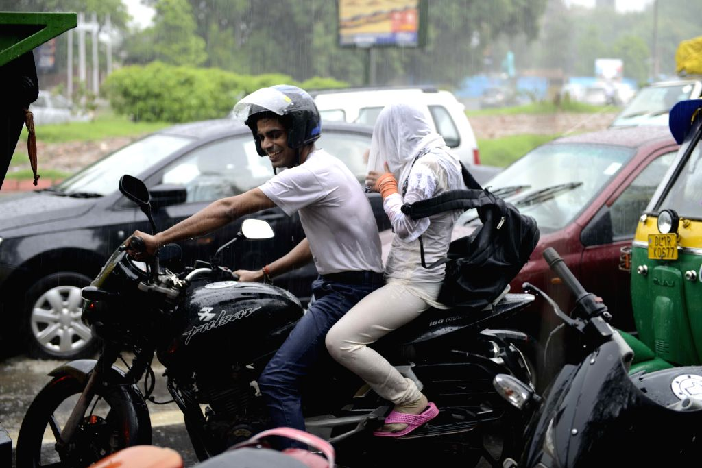 People get drenched during rains in New Delhi on Sept 11, 2014.