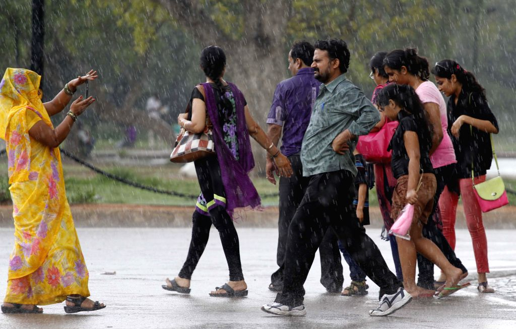 People get drenched on a Delhi road during rains in the national capital on July 17, 2014.