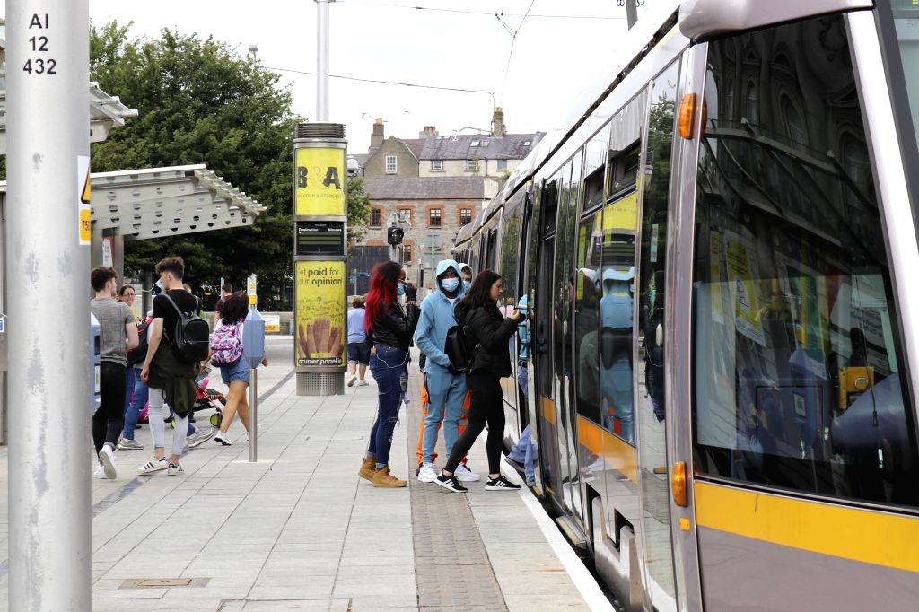People get on a tram in Dublin, Ireland, on July 13, 2020. Wearing a mask or face covering on Ireland's public transport is a must starting from Monday or one could ...