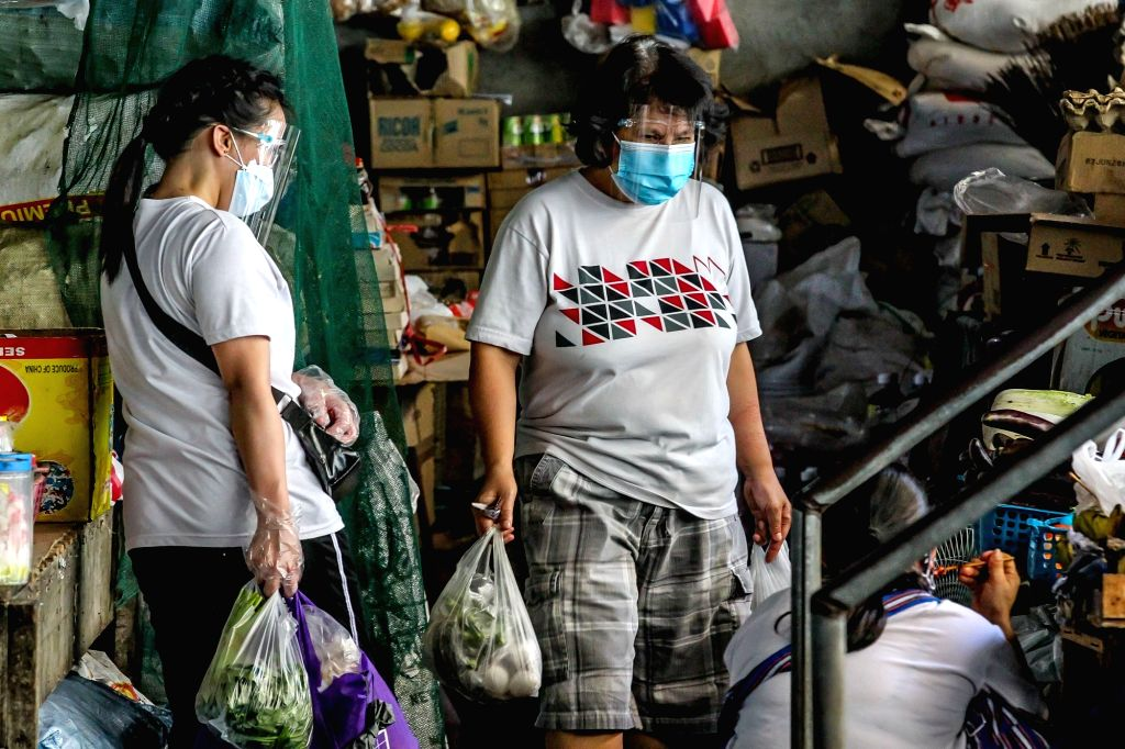 People have their faces protected at a market in Manila, the Philippines on Aug. 14, 2020.   The number of confirmed COVID-19 cases in the Philippines surged to ...