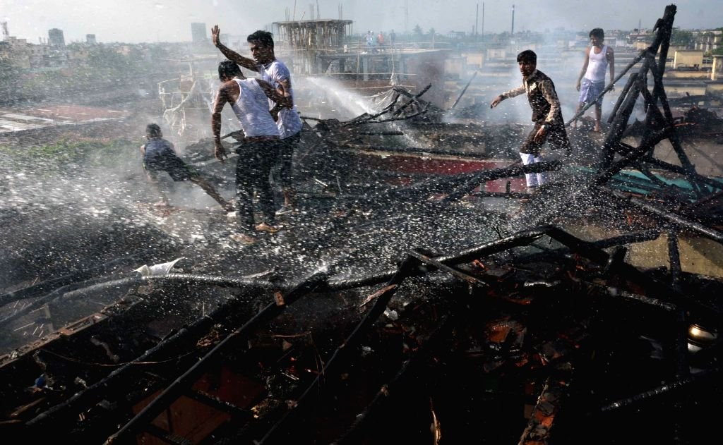 People help firefighters douse fire that broke out in a Kolkata slum on July 9, 2017.