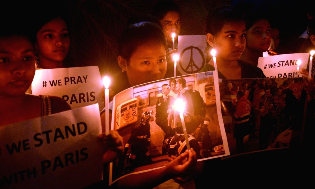 People hold candles to mourn the victims of a series of attacks in Paris; in Agartala on Nov 15, 2015.