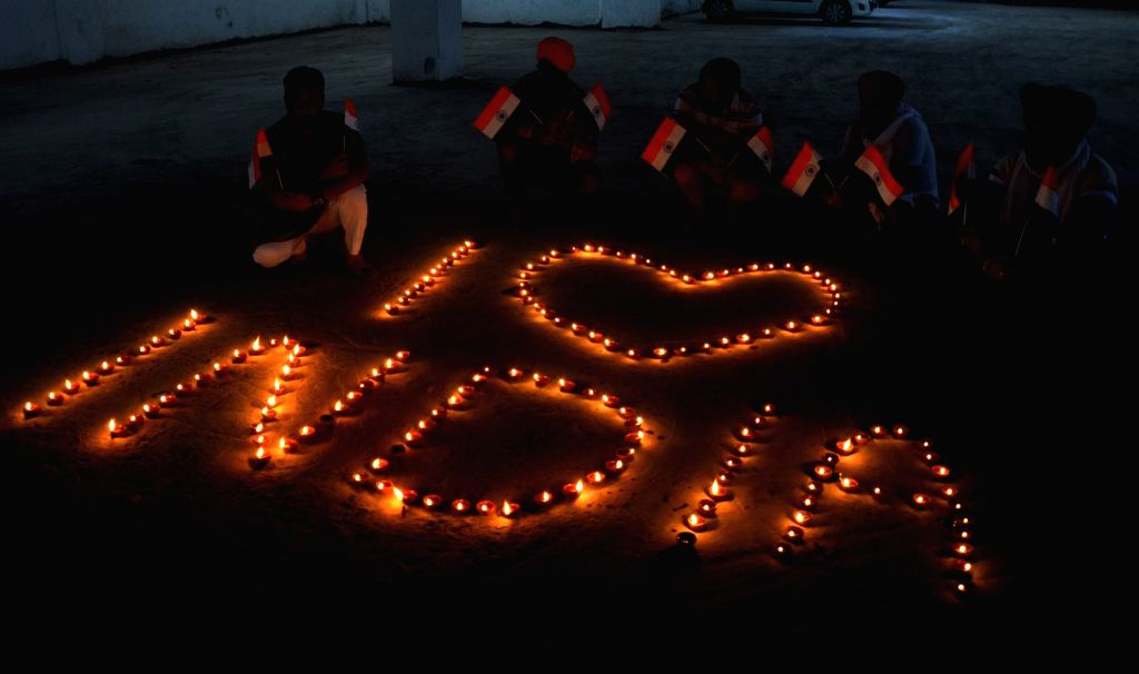 People hold national flags as they pose in front of the burning earthen lamps arranged in the formation of 'I LOVE INDIA' on the eve of the 74th Independence Day, in Amritsar on Aug 14, ...
