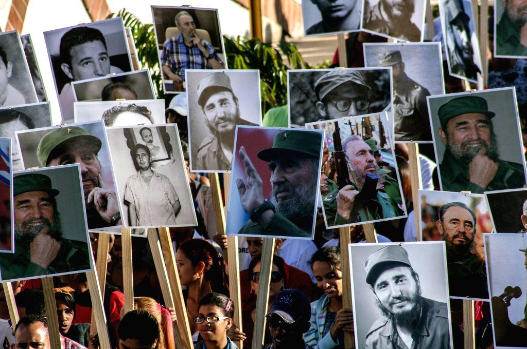 People hold pictures of late Cuban President Fidel Castro during a pilgrimage to the Santa Ifigenia Cemetery in Santiago de Cuba, east Cuba, Dec. 4, 2017. ...