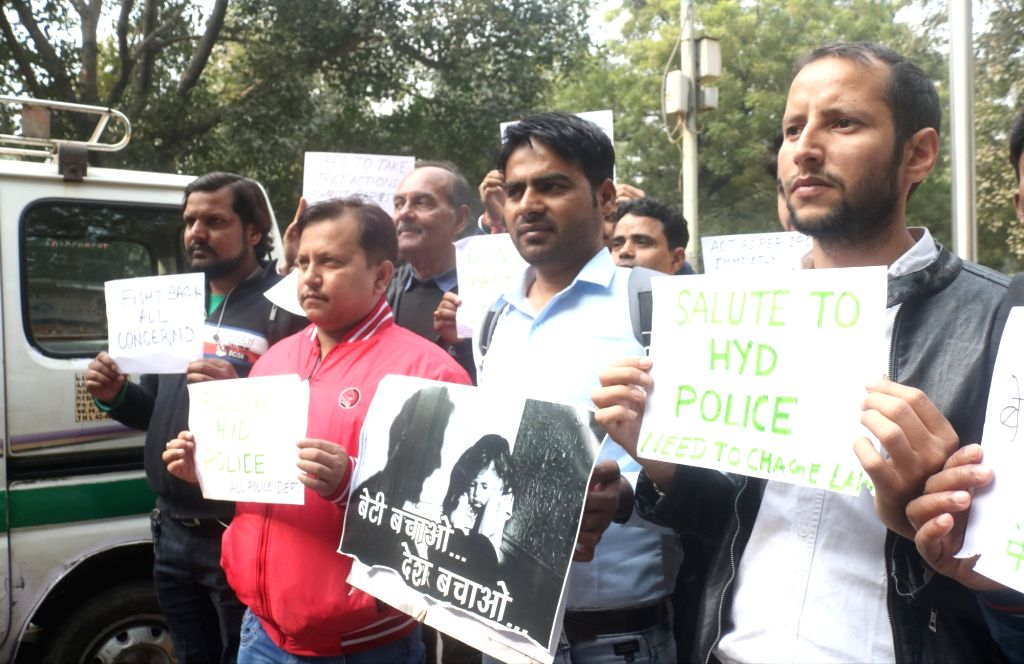 People hold posters congratulating the Hyderabad Police after all the four accused in the brutal gang rape and murder of a young veterinarian in Hyderabad, were killed in a police ... - Ranga Reddy