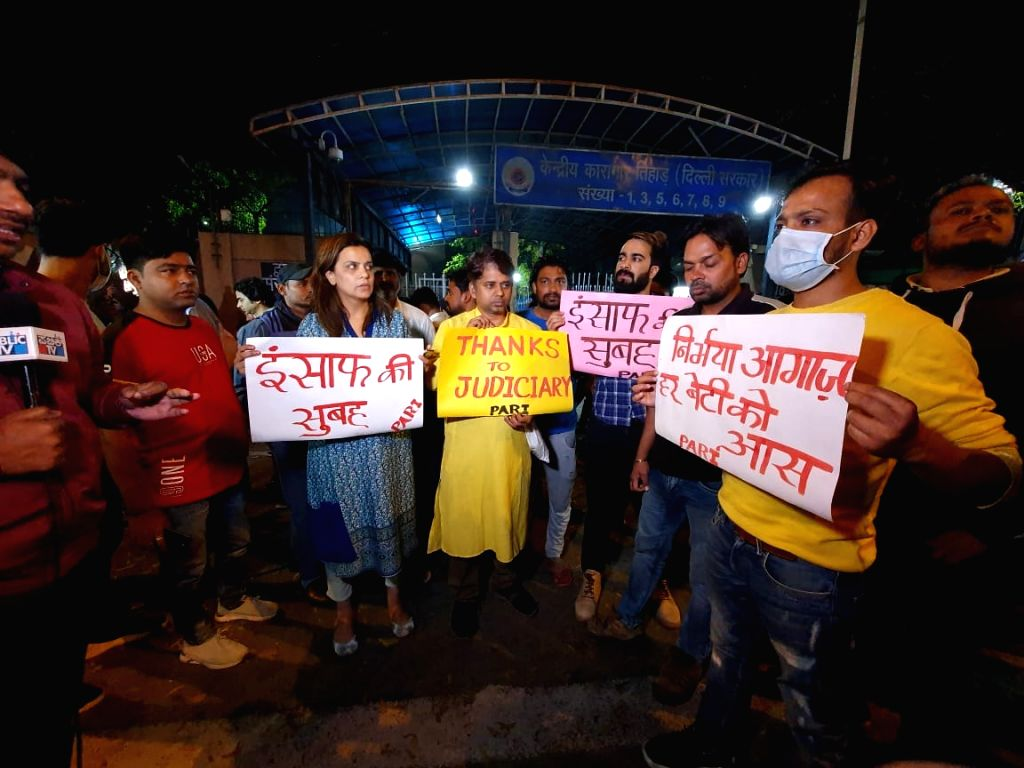 People hold posters outside the Tihar Jail ahead of the hanging of four convicts in the 2012 Nirbhaya rape case, in New Delhi on March 20, 2020.