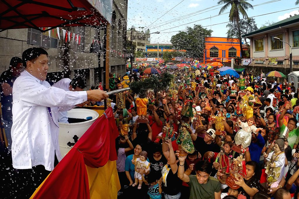 People hold statues of the Santo Nino during the Feast of the Santo Nino in Manila, the Philippines, Jan. 17, 2016. The Philippines held weekend celebrations to mark ...