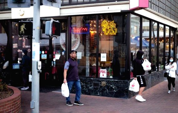 People holding take-away food walk past a restaurant on a business street in San Mateo, California, the United States, March 26, 2021.