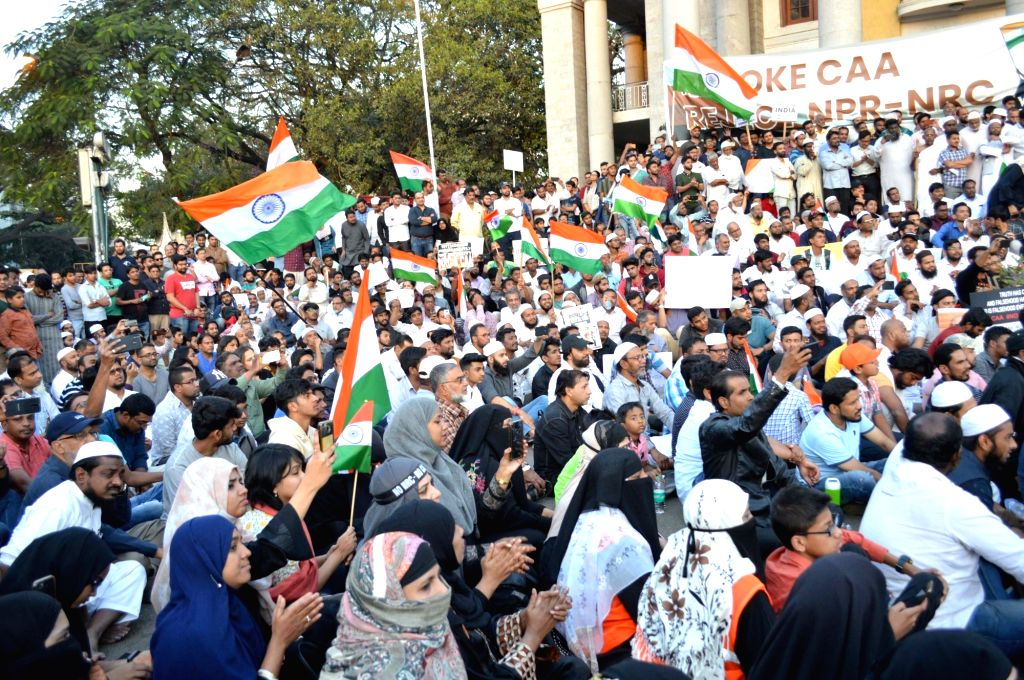 People holding tricolors participate in a protest the Citizenship Amendment Act (CAA) 2019, National Register of Citizens (NRC) and National Population Register (NPR), in Bengaluru on Jan ...