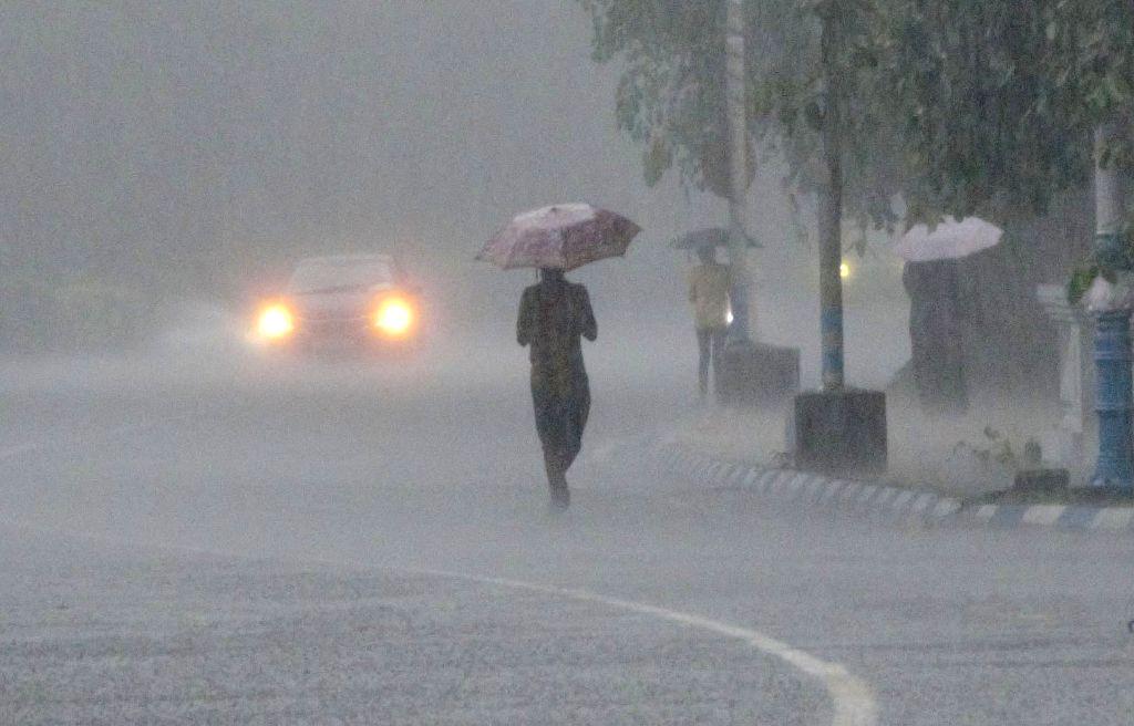 People holding umbrellas during rainfall in Kolkata on Monday June 14, 2021.
