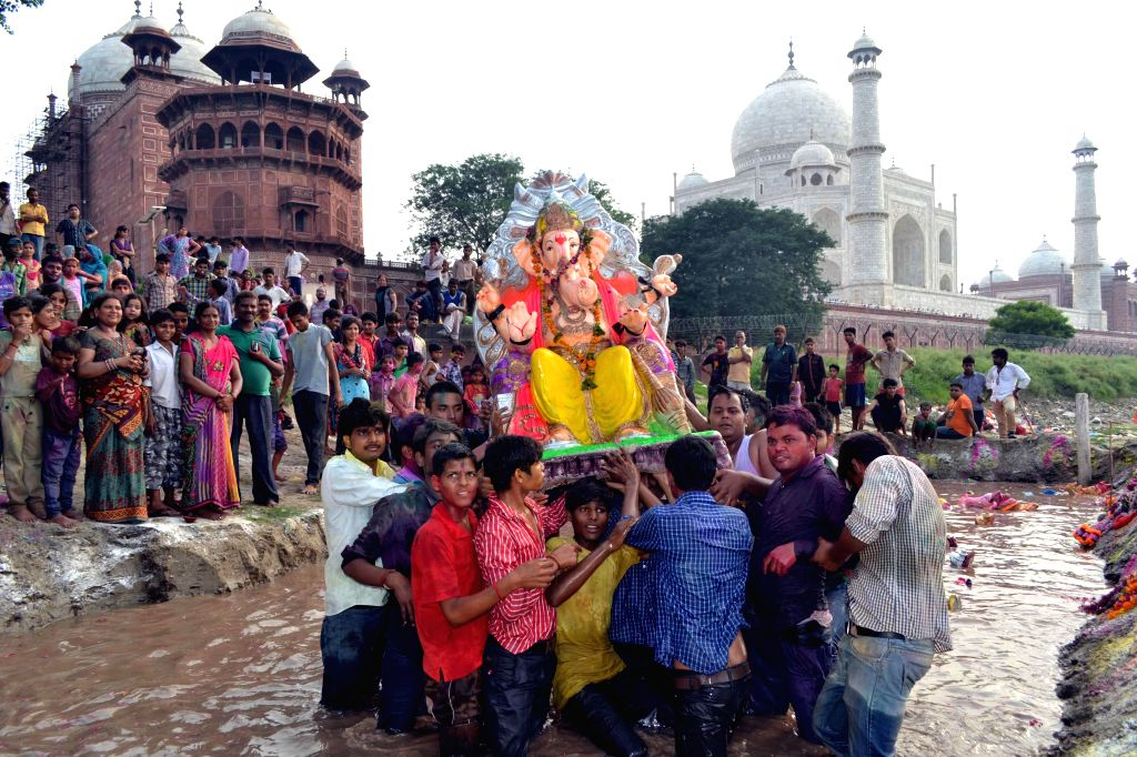 People immerse a Ganesh idol in a pond after Ganesh Festival in Agra on Sept 7, 2014.