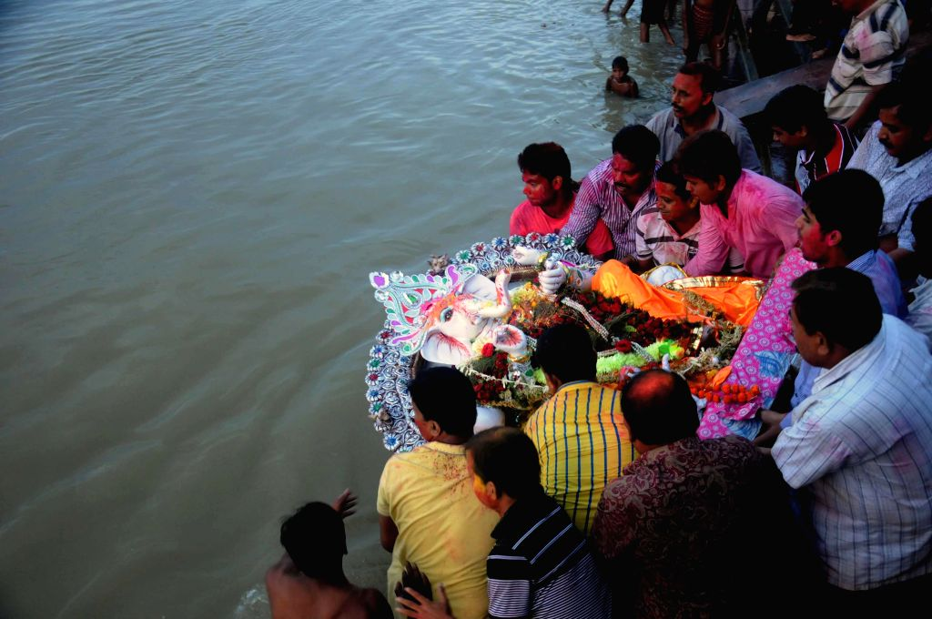 People immerse a Ganesh idol in the Hooghly river in Kolkata on Aug 31, 2014.