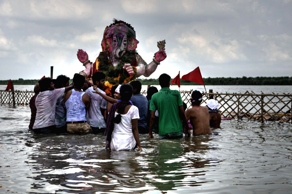 People immerse an idol of lord Ganesh in the Yamuna river after Ganesh festival in New Delhi on Sept 8, 2014.