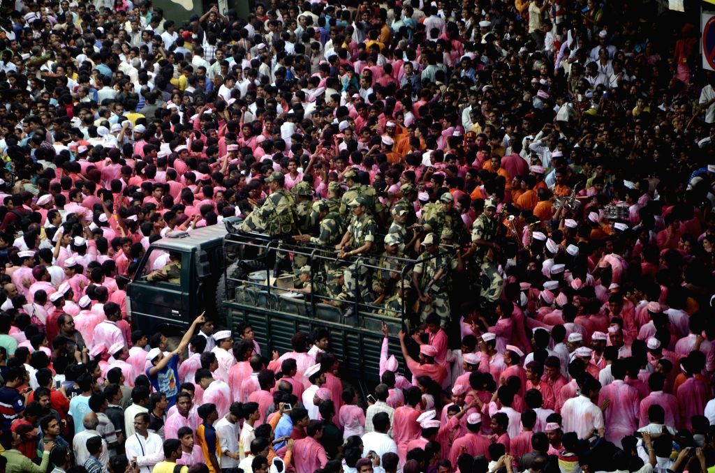 People in large numbers participate in a Ganesh idol immersion procession under the supervision of BSF in Mumbai on Sept 8, 2014.
