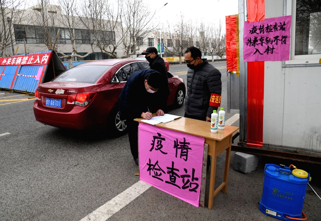 People inspect passengers and vehicles at Sancun Village in Jiangshan Town of Laixi City, east China's Shandong Province, Jan. 28, 2020. TO GO WITH XINHUA HEADLINES ...