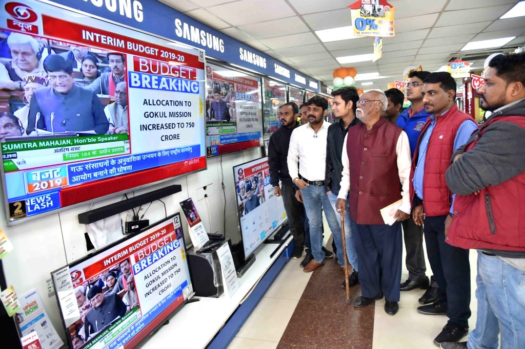 People keep a close eye as Union Finance Minister Piyush Goyal presents the interim budget 2019, at an electronics store in Patna, on Feb 1, 2019. - Piyush Goyal