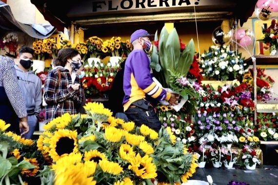 People leave the Los Angeles Flower Market with their purchases in downtown Los Angeles, California, the United States, Feb. 14, 2021.