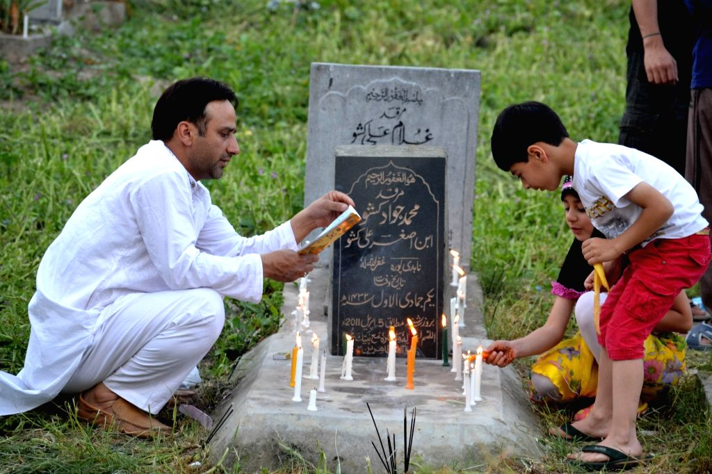 People light candles on the grave of their ancestors on Shab-e-barat in Srinagar, on May 22, 2016.