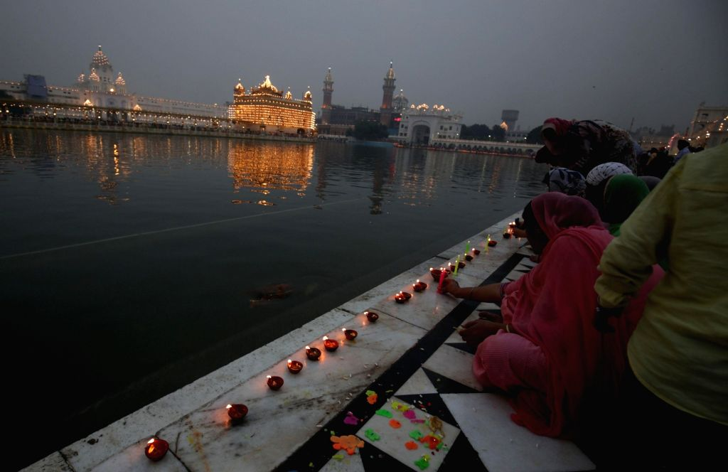 People light earthen lamps at the Golden Temple on Diwali in Amritsar on Oct 30, 2016.