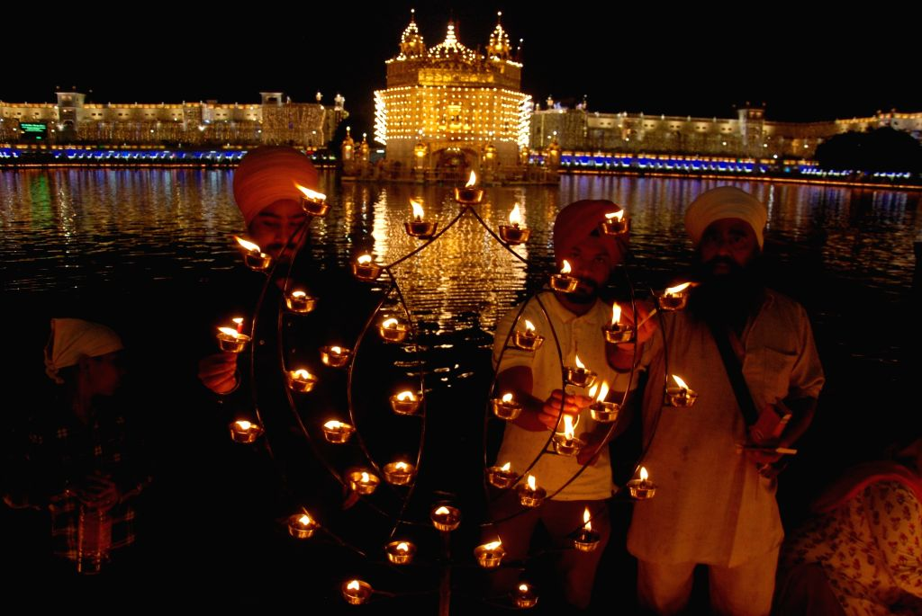 People light earthen lamps during Diwali celebrations, at Golden Temple in Amritsar on Oct 27, 2019.