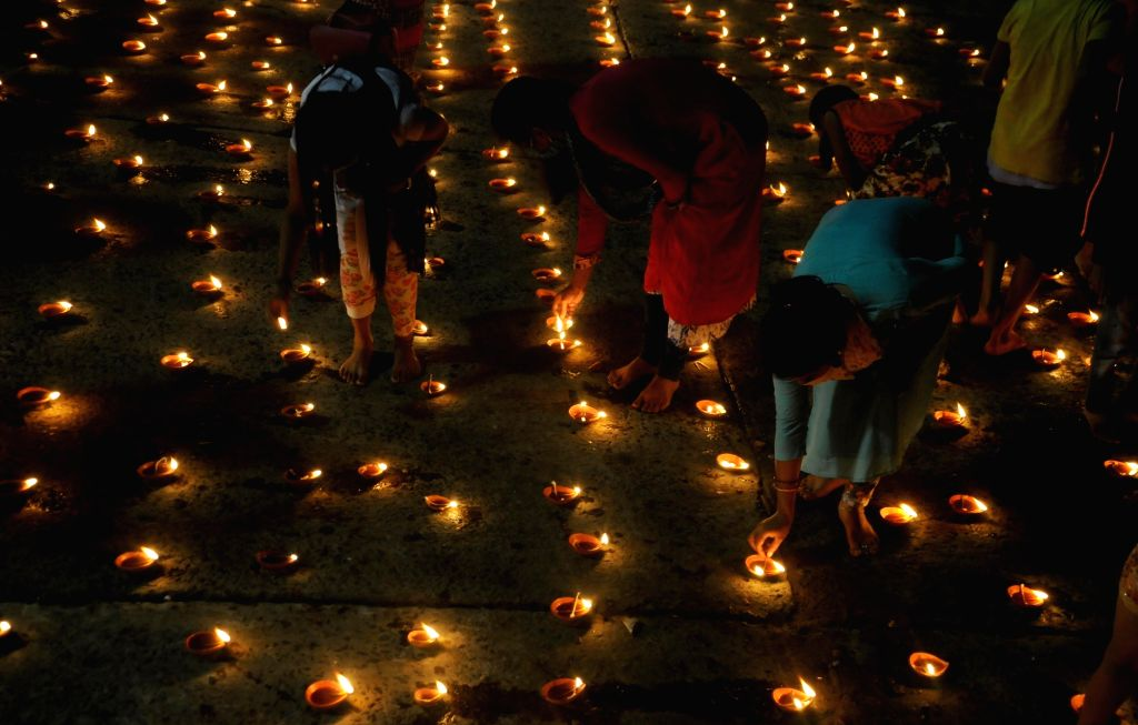 People light up earthen lamps on the banks of Ganga river on the occasion of Kartik Purnima also known as Dev Deepawali, at Nimtala Ghat in Kolkata on Nov 30, 2020.