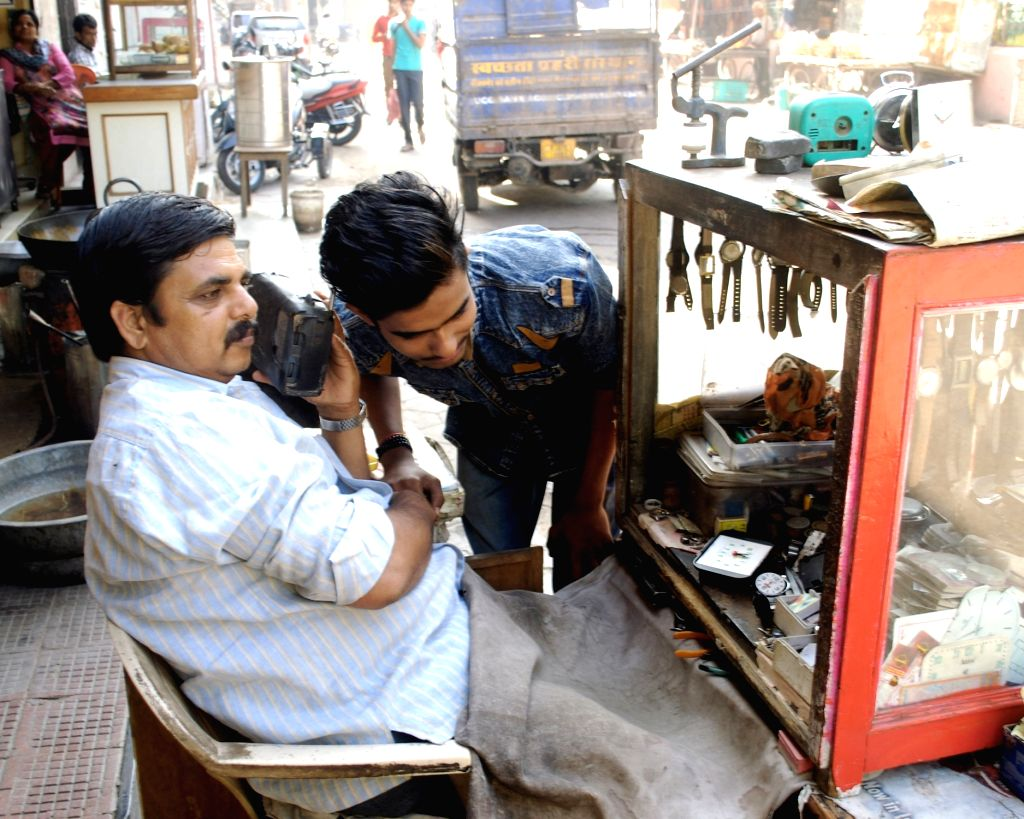 "People listening to Prime Minister Narendra Modi's ""Mann Ki Baat"" on a radio set in Bikaner. - Narendra Modi"