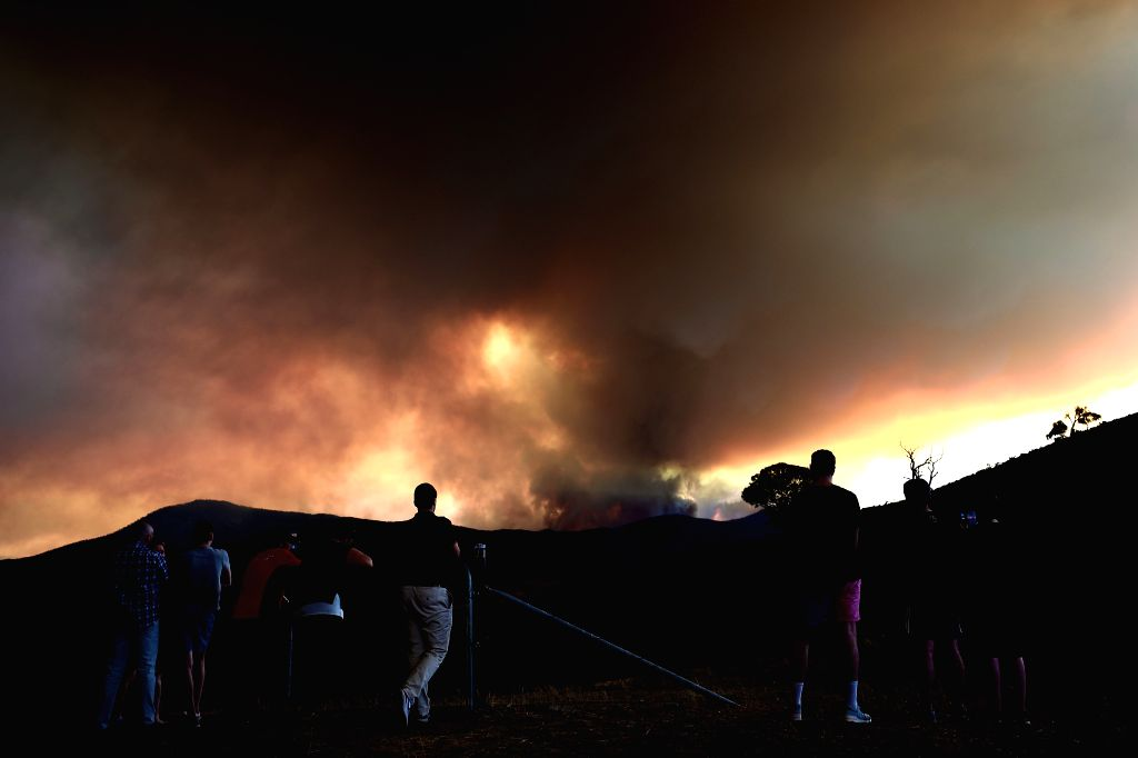 People look at a bushfire at the Namadgi National Park in Canberra, Australia on Jan. 28, 2020.   A bushfire in the south of Canberra is recognized as the most ...