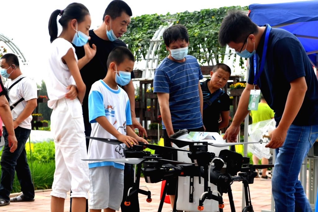 People look at an agricultural drone at the 19th China Changchun International Agriculture and Food Fair Expo, in Changchun, northeast China's Jilin Province, ...