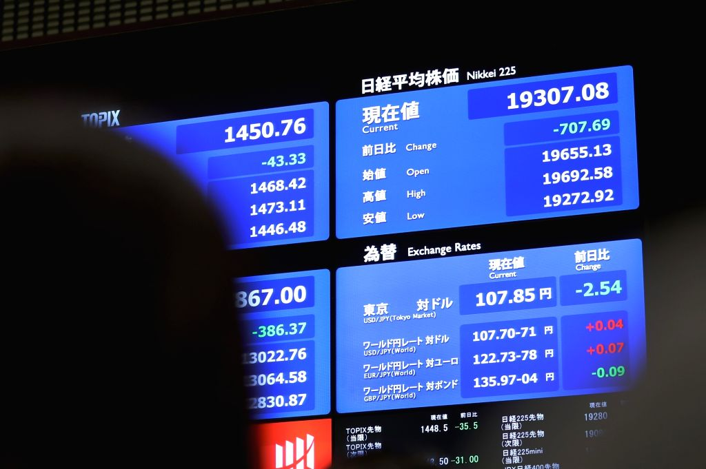 People look at an electronic board displaying stock prices at the Tokyo Stock Exchange in Tokyo, Japan, Jan. 4, 2019. Tokyo stocks opened sharply lower on Friday, with the benchmark Nikkei stock index tracking an equities rout on Wall Street overnigh