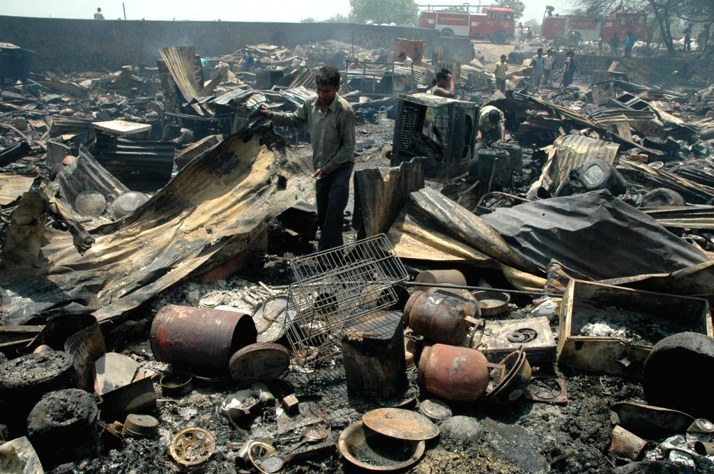 People look at their houses which were destroyed in a massive fire that broke out in a slum cluster of south Delhi''s Vasant Kunj on April 25, 2014.