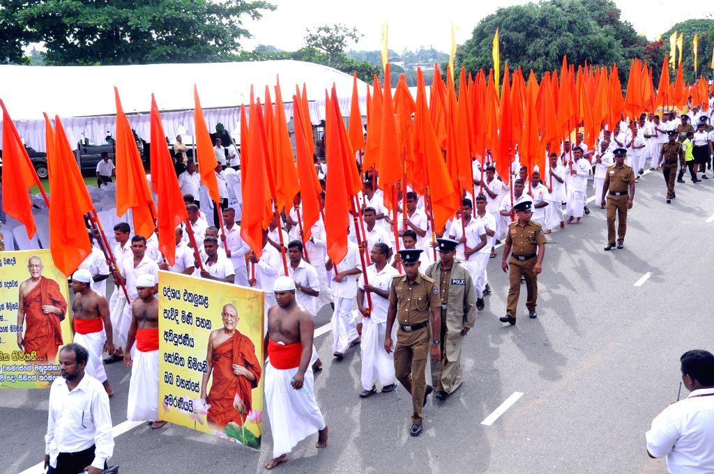 People march during the funeral of the Venerable Maduluwawe Sobitha, an influential monk who passed away on Nov. 8, in Colombo, Sri Lanka, Nov. 12, 2015. Maduluwawe ...