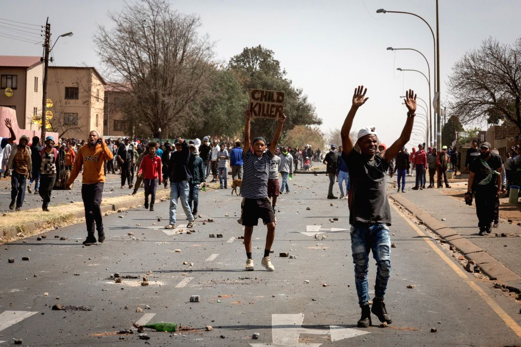 People march on a road during a protest over the death of a teenager in Eldorado Park, Johannesburg, South Africa, Aug. 27, 2020. South African President Cyril ...