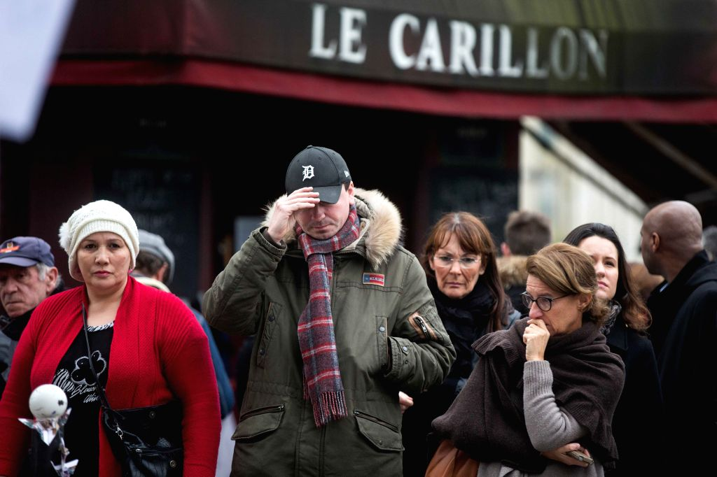 People mourn during a one-minute silence for the victims of the terror attacks in Paris, France, on Nov. 16, 2015.