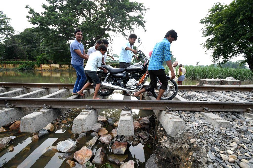 People move over a bridge in the flood hit Chanpatia, Bihar on Aug 18, 2017.