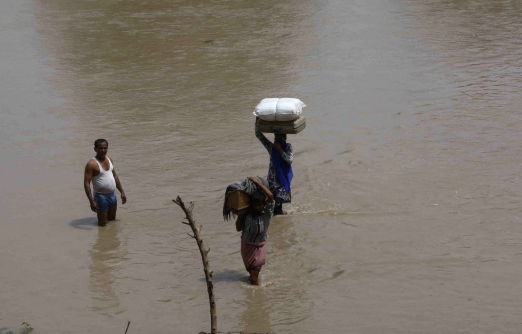 People move to higher lands after water level increased in the Yamuna river, in New Delhi, on July 30, 2018.