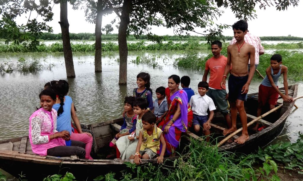 People move to higher lands from flood hit villages in Begusarai district of Bihar on Aug 18, 2016.