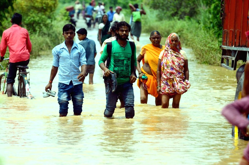 People move to higher lands from from a flood hit village in Patna district of Bihar on Aug 16, 2016.