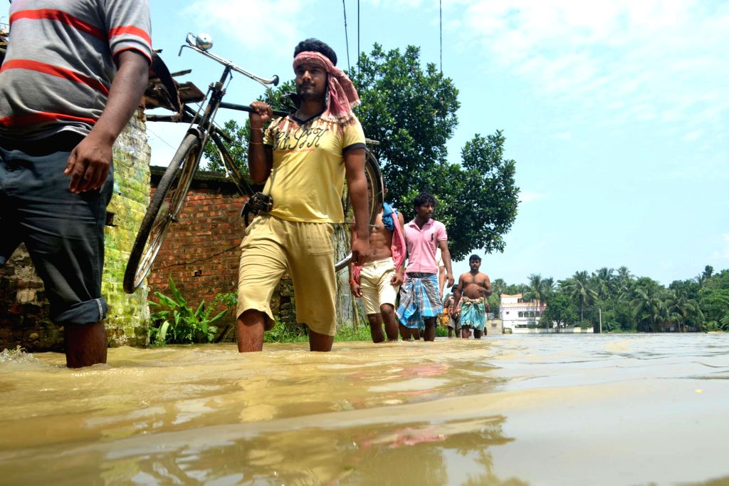 People move towards higher lands from flooded hit Amta in Howrah of West Bengal on Aug 5, 2015.