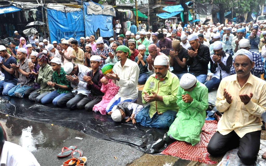 People offer namaz on the last Friday of Ramadan amid rains outside Tipu Sultan Mosque in Kolkata on June 23, 2017.