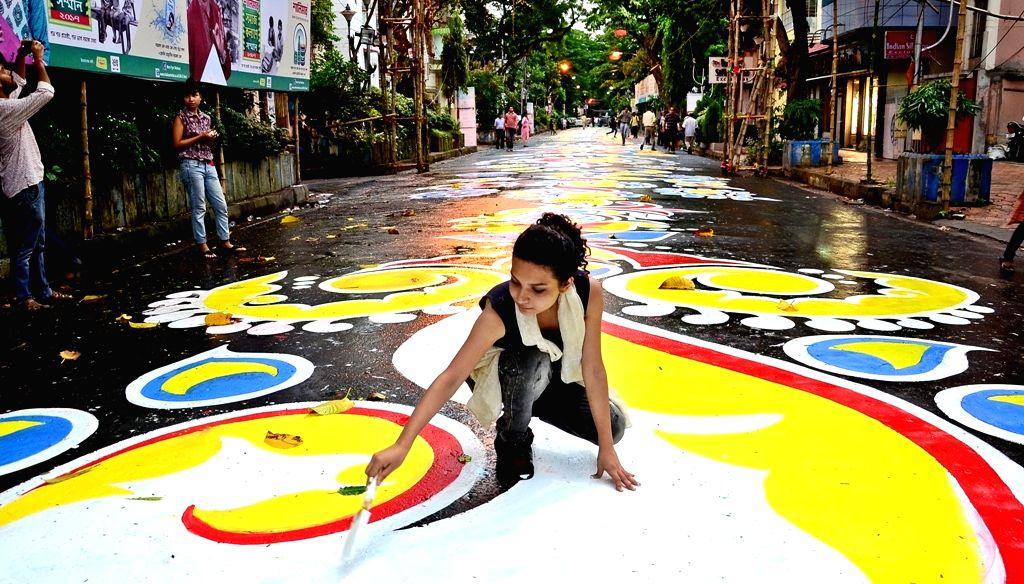 "People paint a street, popularly known as ""alpona"" in a bid to create longest street art ahead on Durga Puja festival in Kolkata on Sept. 19, 2017."