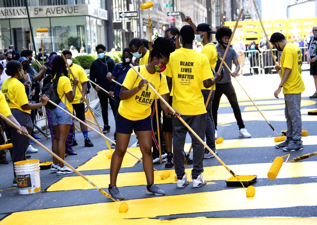 """People paint """"Black Lives Matter"""" mural in front of Trump Tower in New York, the United States, on July 9, 2020. A giant, yellow """"Black Lives ..."""