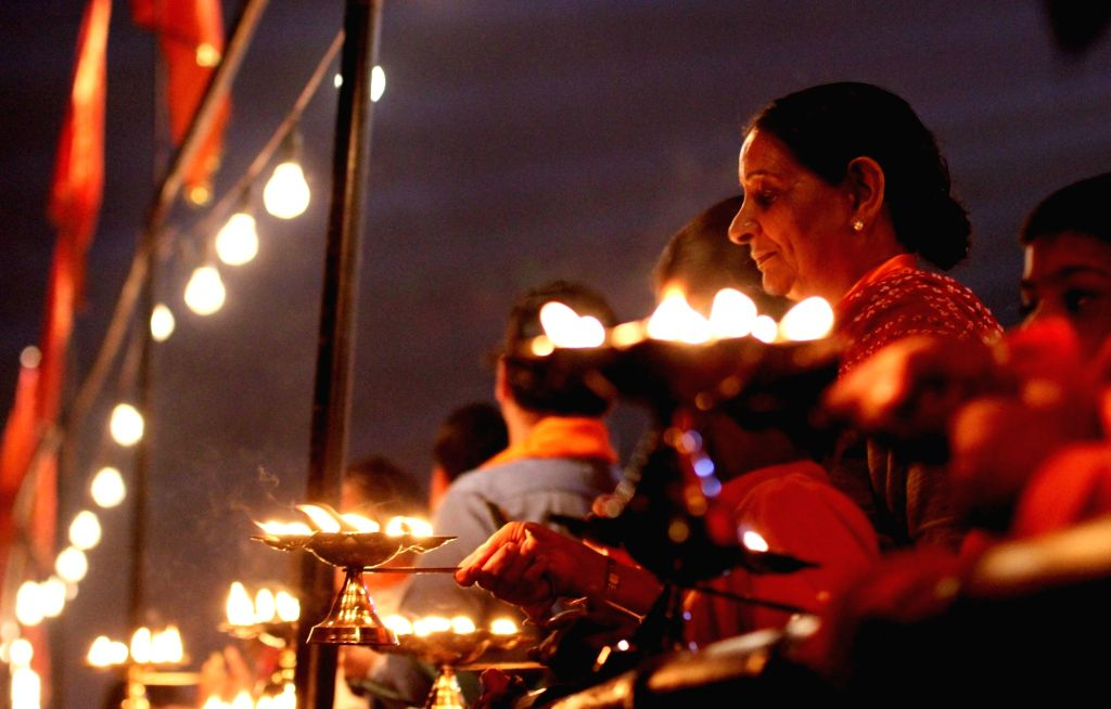 People participate during a `Yamuna Aarti` in New Delhi on Nov. 13, 2015.