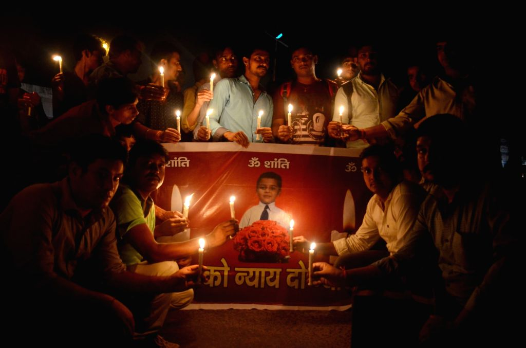 People participate in a candle light vigil over death of 7-year-old Pradyuman who was found dead by a school staff in Ryan international School's washroom with his throat slit; in Gurugram ...