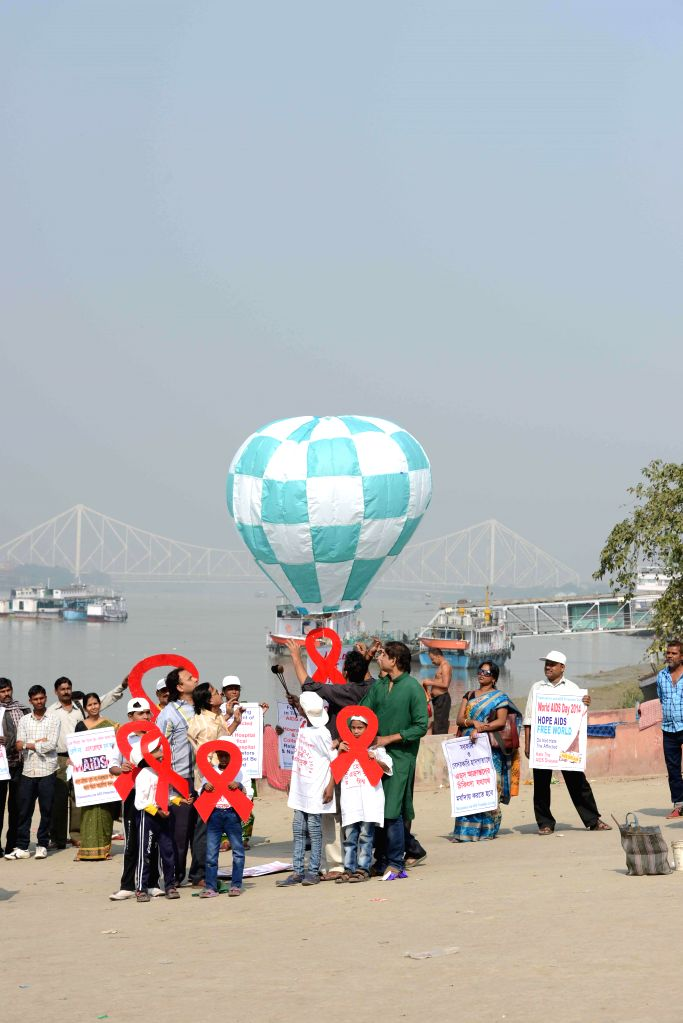 People participate in an AIDS awareness campaign on the eve of World AIDS Day in Kolkata, on Nov 30, 2014.